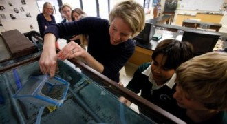 Checking on trout raised in her classroom.