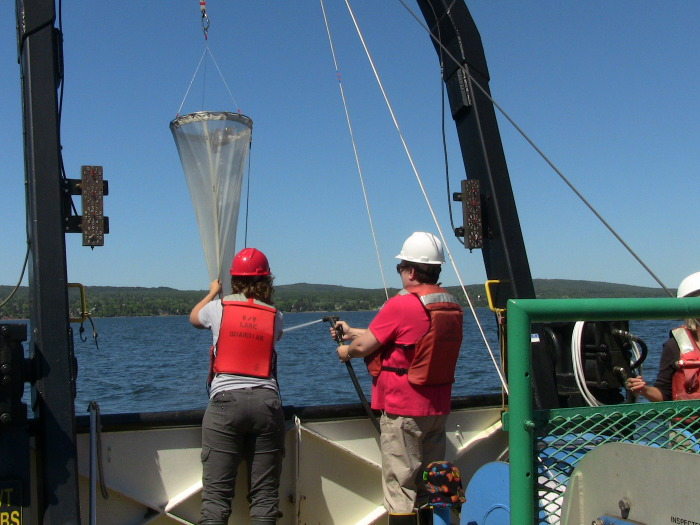 Educator rinsing down a plankton net on Lake Superior in 2011.