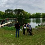 Students outdoors examining specimens collected from a nearby lake