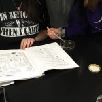 Students using a key to identify macroinvertebrates they collected